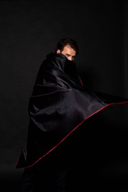 man covering face with cloak of halloween costume on black