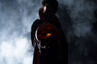 selective focus of man holding pumpkin on black with smoke