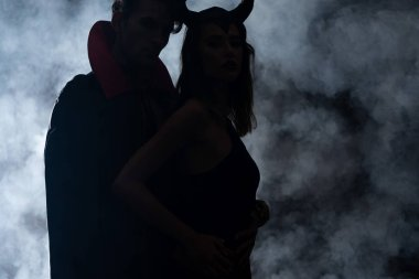 silhouette of man and woman in halloween costumes standing on black with smoke