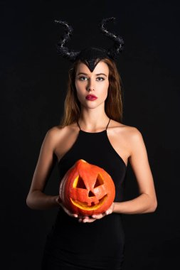 Attractive woman with horns holding halloween pumpkin isolated on black stock vector
