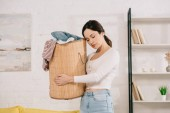 Photo young, tired housewife standing with closed eyes and holding laundry basket