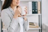 kivágott kilátás fiatal titkár kezében kávéscsésze az irodában