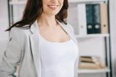 levágott kilátás fiatal, mosolygós titkárnő áll az irodában