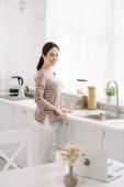 selektivní zaměření kuchyňského stolu s notebookem v blízkosti usměvavé ženy stojící v blízkosti dřezu