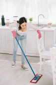 Fotografie young housewife in blue jeans washing floor in kitchen with mop