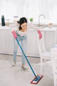Fotografie junge Hausfrau in Blue Jeans wäscht Fußboden in Küche mit Wischmopp