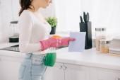 oříznutý pohled na ženu v domácnosti držící láhev spreje a hadr v kuchyni
