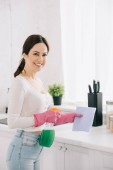 cheerful housewife looking at camera while holding spray bottle and rag in kitchen