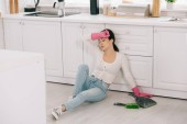 Photo exhausted housewife sitting on floor in kitchen near scoop and brush