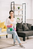 Fotografie attractive housewife looking at camera while sitting on table and holding rag and spray bottle