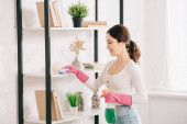 Fotografie happy housewife cleaning rack with rag and holding spray bottle with detergent