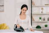 Photo beautiful housewife smiling while ironing on ironing board