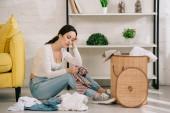 Fotografie Müde Hausfrau sitzt auf dem Boden neben Kleidung und Wäschekorb