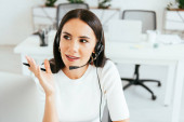 selective focus of attractive broker looking away while holding pen in call center
