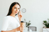 happy broker touching headset and holding paper cup