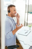 selective focus of happy broker touching headset and gesturing on office