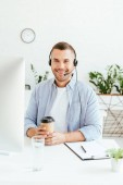 Photo cheerful operator in brokers agency holding coffee to go