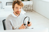 handsome bearded operator in brokers agency holding headset