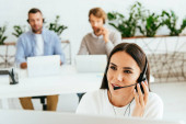 Photo selective focus of broker touching headset near coworkers in office