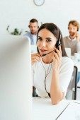 selective focus of attractive broker touching headset near coworkers in office