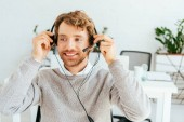 Photo happy bearded broker touching headset and smiling in office