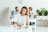 Photo selective focus of attractive broker with pen touching headset near coworkers
