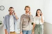 Photo cheerful brokers in headsets standing and looking at camera