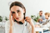 Müder Makler mit Kopfschmerzen bei Mitarbeitern im Büro