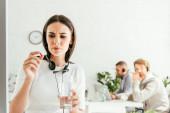 Selektiver Fokus kranker Makler mit Tablette und Glas Wasser in der Nähe von Mitarbeitern im Büro