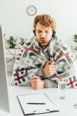 Kranker bärtiger Makler in Decke gehüllt im Büro
