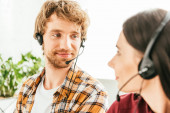 selective focus of bearded broker looking at attractive coworker