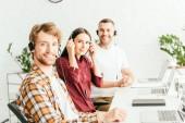 Selektiver Fokus des bärtigen Maklers im Headset neben gut gelaunten Mitarbeitern im Büro
