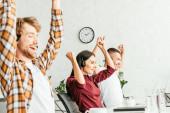 Selektive Fokussierung glücklicher Makler mit Händen über dem Kopf im Amt