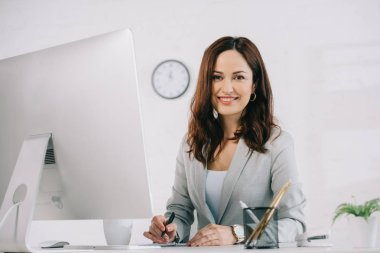 Beautiful, smiling secretary looking at camera while sitting at workplace near computer monitor stock vector