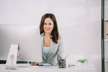 attractive, smiling secretary looking at camera while sitting at workplace