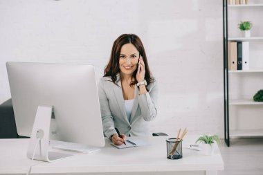 smiling secretary talking on smartphone, looking at camera and writing in notebook while sitting at workplace