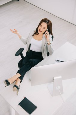 high angle view of cheerful, elegant secretary talking on smartphone while sitting at workplace