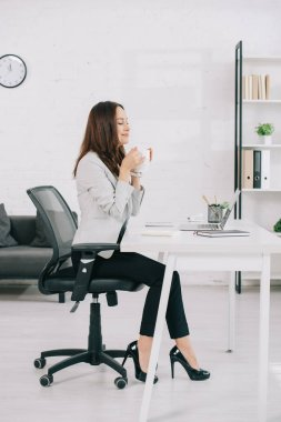 Elegant, young secretary sitting at workplace with closed eyes while holding coffee cup stock vector