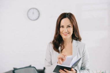 beautiful, smiling secretary looking at camera while writing in notebook