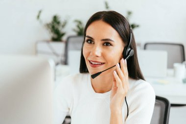 Selective focus of attractive broker touching headset while working in call center stock vector