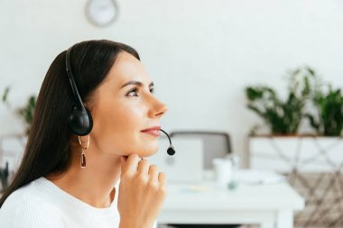 smiling broker in headset in modern office