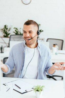 happy operator in brokers agency showing shrug gesture in office
