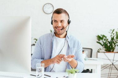 Happy operator in brokers agency gesturing while looking at computer monitor stock vector