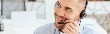 panoramic shot of happy and handsome operator in brokers agency touching headset