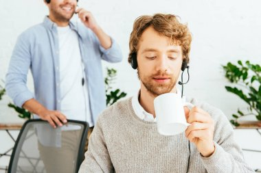 Selective focus of handsome bearded broker holding cup near coworker in office stock vector