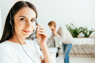 Selective focus of beautiful broker touching headset near coworker in office stock vector