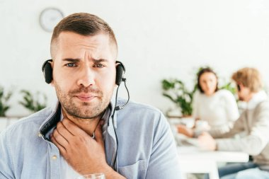 selective focus of broker with sore throat looking at camera in office