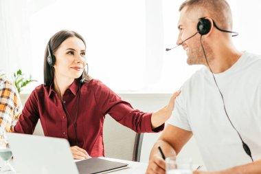 Selective focus of broker touching happy coworker in office stock vector