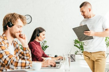 Selective focus of broker holding clipboard near operators in office stock vector