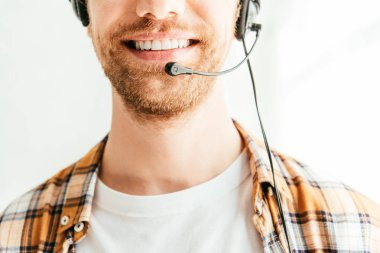 cropped view of bearded broker in headset smiling in office